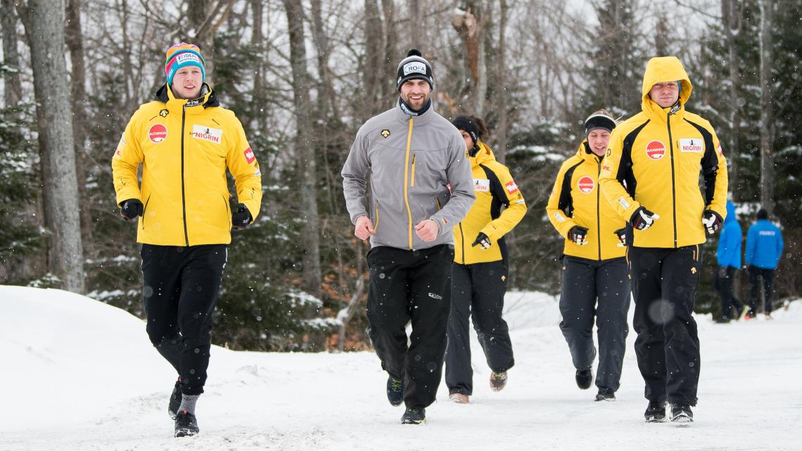Die Bobsportler joggen bei Schneegestöber – im Vordergrund von links: Alexander Schüller, Christoph Hafer und Francesco Friedrich. (Foto: Viesturs Lacis)